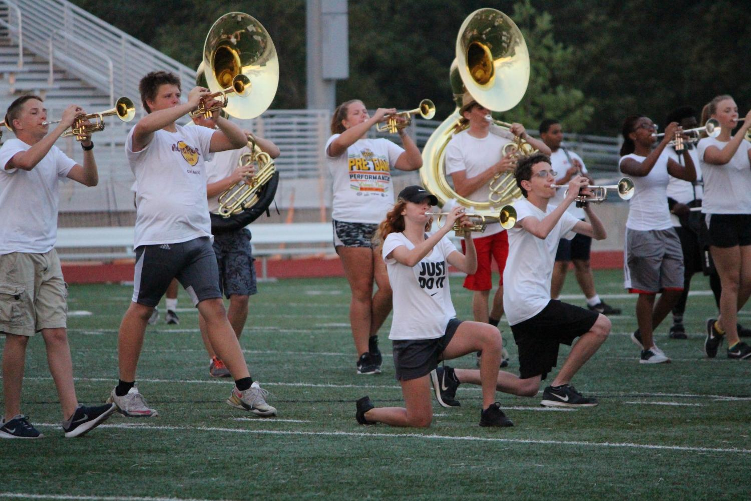 Ethan Wiedmier stands in a pose playing his trumpet while Grace Baer and Andrew Downs kneel while playing their trumpets during a halftime show.