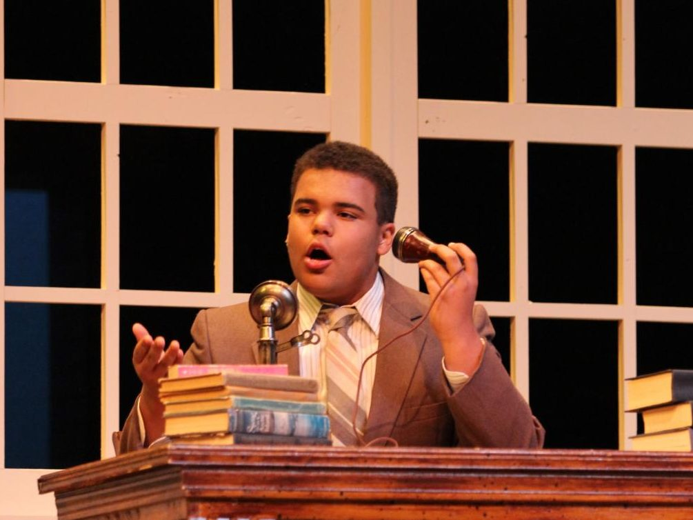 Gabriel Watkins-Mocumbi, playing Daddy Warbucks, talks through the phone to the president in the school musical,
