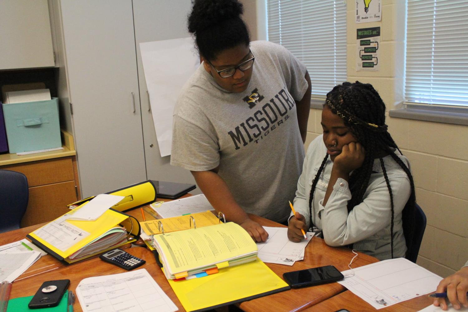Amaya Daniels helps Anyha Cain with geometry honors in Mr. Collins.