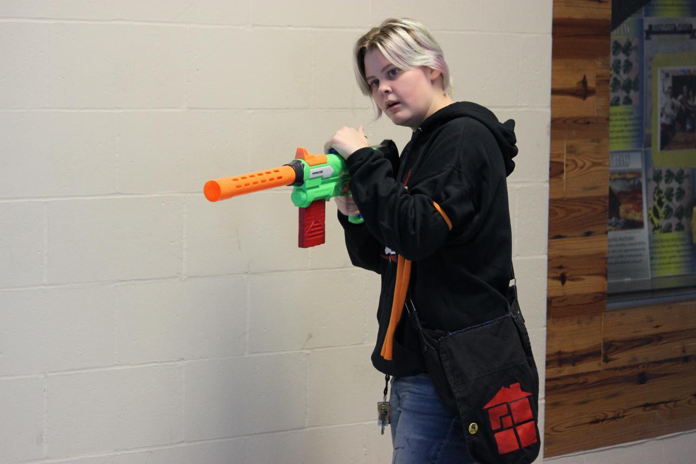 Seairra Ferguson aims nerf gun at zombie.