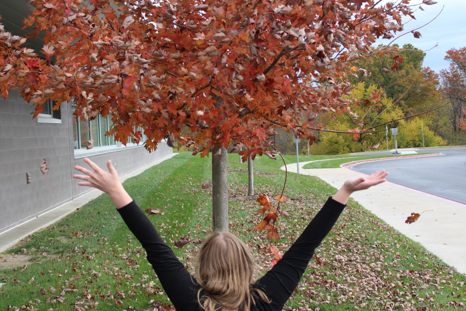 A student happily throws leaves in the air. (Allison Collier)